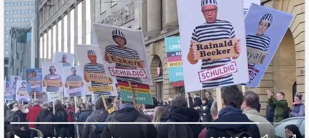 Plakte: Wissenschaftler und Politiker in Sträflingskleidung bei Querdenken